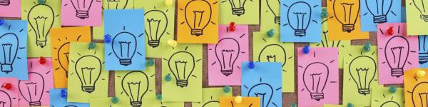 An image of lightbulbs drawn on sticky notes conceptually describing data analysis.